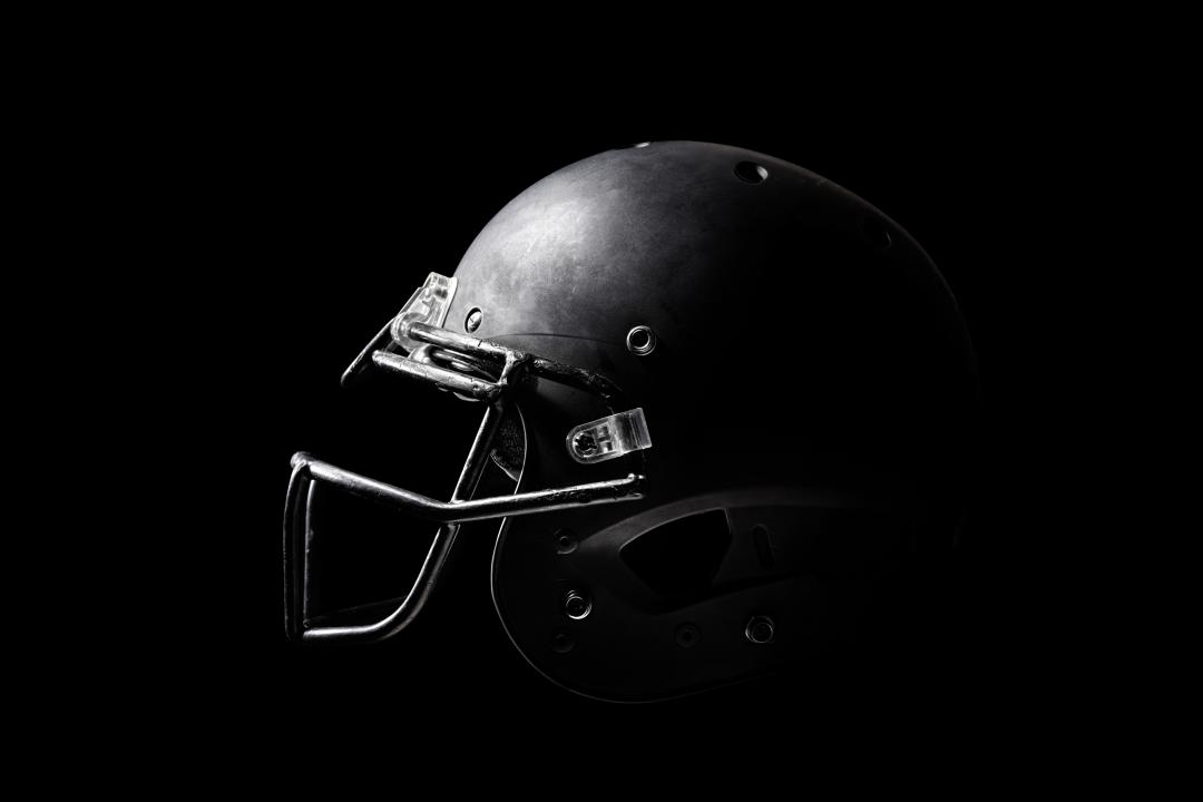Black and white photo of a football helmet on a black background