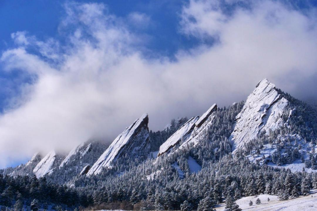 Photo of the flatirons above Boulder, Colorado covered in snow.