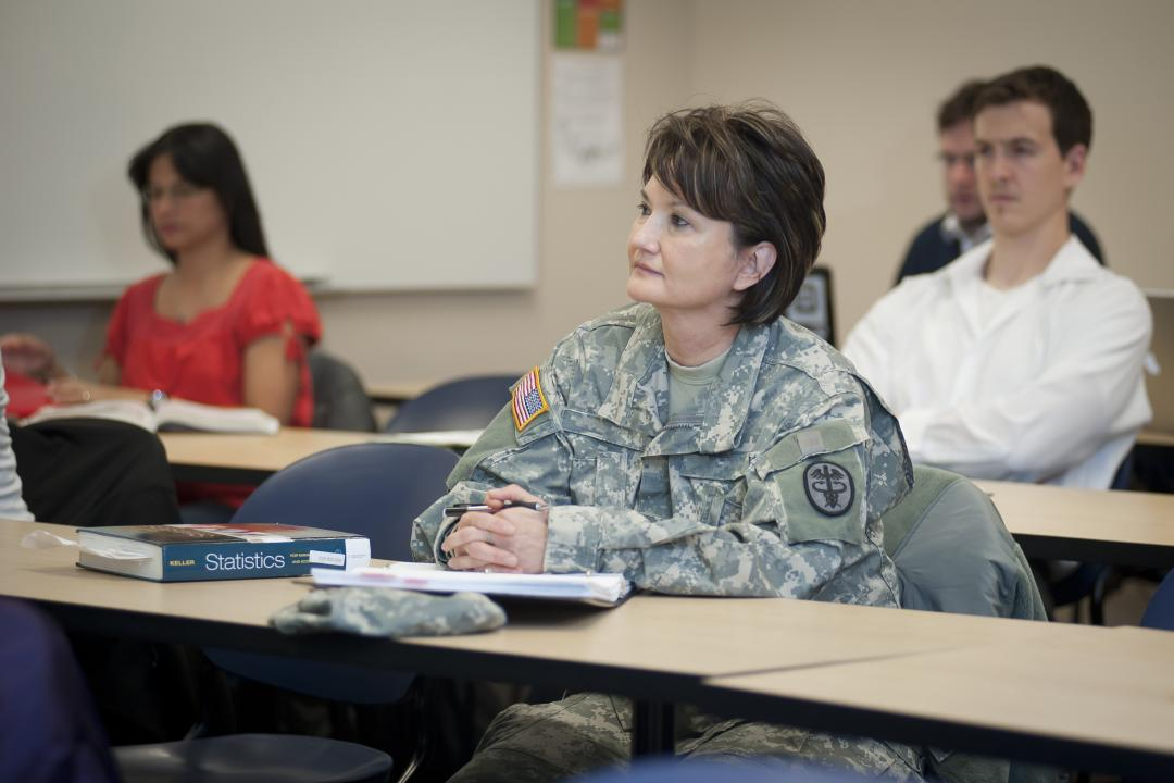 Photo of student soldier from UCCS sitting at a table in a classroom.