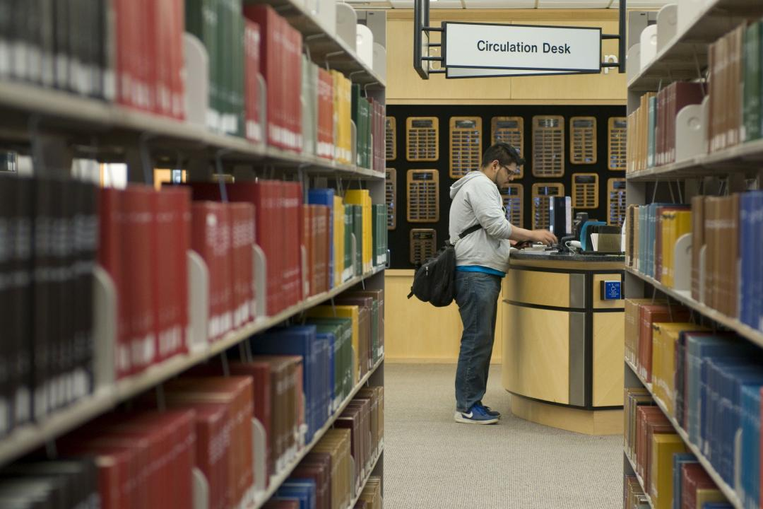 Photo of a student standing at the circulation desk in the UCCS Kraemer Family Library.