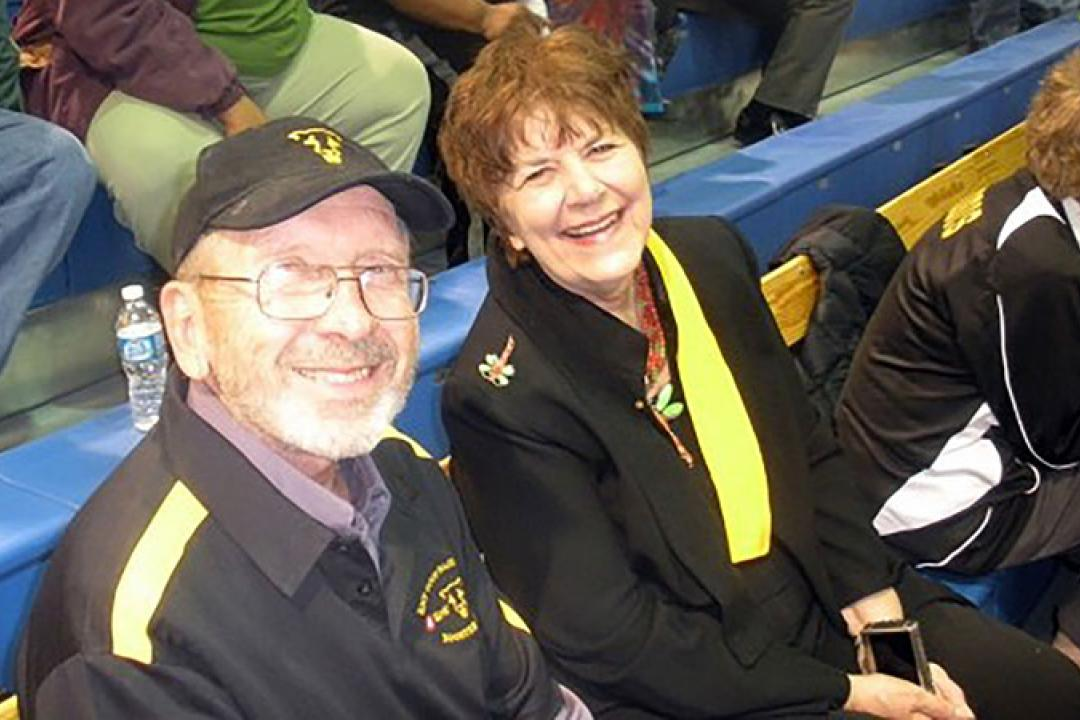 Photo of Al and Carole Shoffstall seated in the stands of an athletic event.