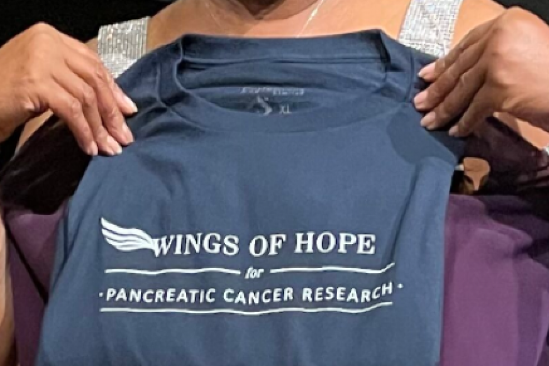 """Photo of a woman's hands holding up a T-shirt that reads: """"Wings of Hope for pancreatic cancer research."""""""