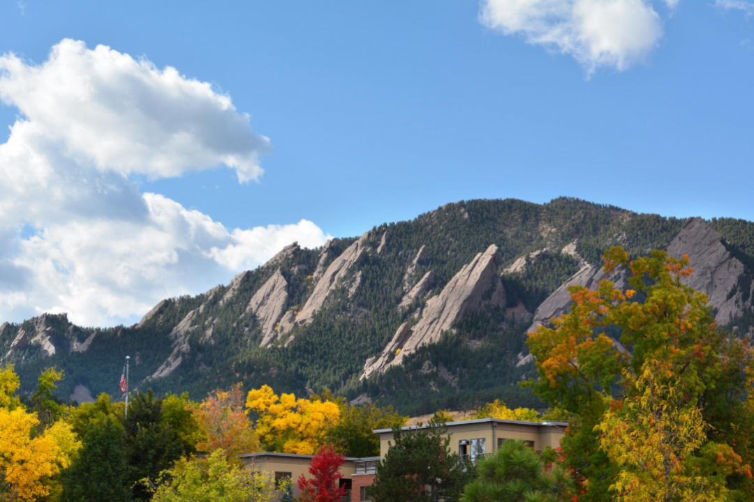 Photo of the Boulder Flatirons rising above trees with autumn leaves in the foreground.