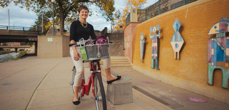 Graduate Coordinator Jessica Halliday pictured on a bicycle near CU Denver